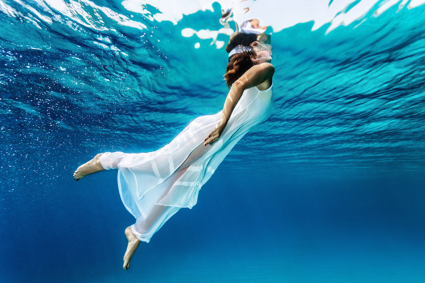 Nice girl emerges from the sea, swimming underwater, enjoying nice refreshing water, wearing long dr