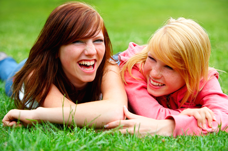 Two young teens relaxing in a park.