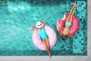 Dvi merginos mėgaujasi atostogomis baseine