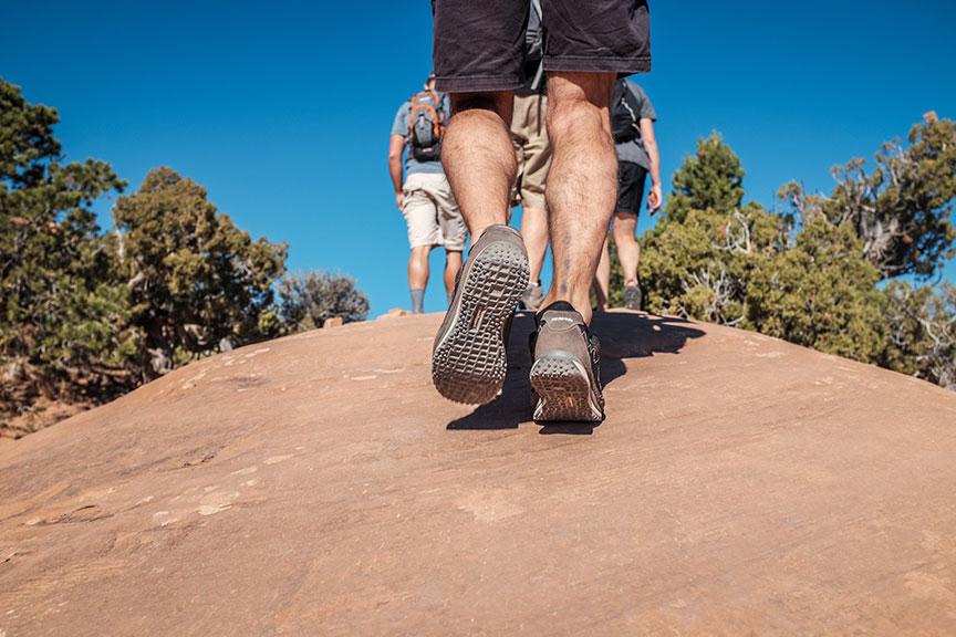 Į kalną žygiuojančių vyrų kojos