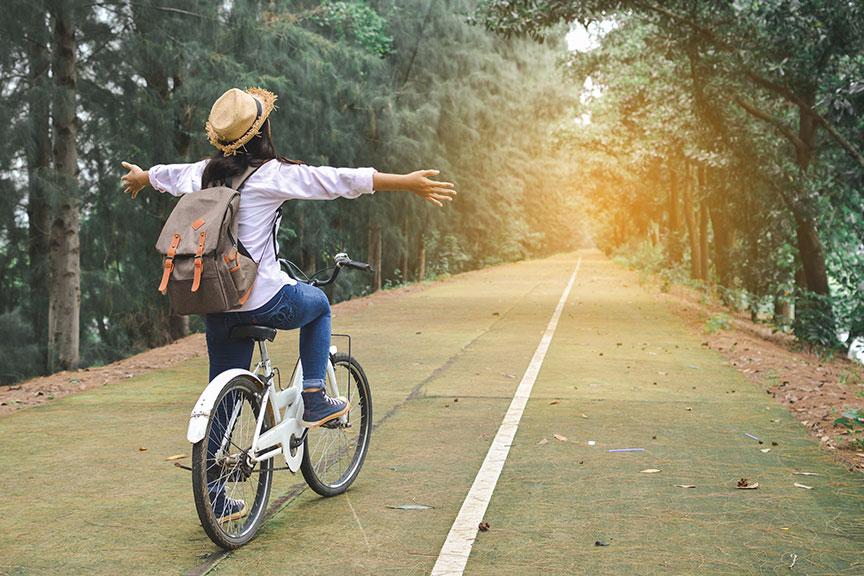 Laiminga mergina keliaujanti dviračiu