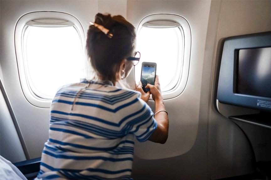 Moteris fotografuoja pro lėktuvo langą, Aeoroflot - Russian Airlines
